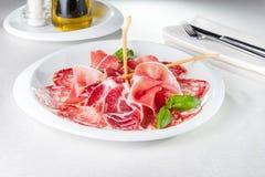 Sortiment av kött, salami, skinka och bacon för matvaruaffär kallt italienskt på maträtt Royaltyfria Bilder