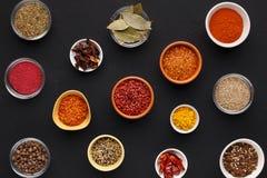Sortiment av kryddor i bunkar på svart bakgrund arkivbild