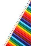 Sortiment av kulöra blyertspennor över vit Arkivbild