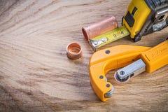 Sortiment av mässingsvattenrörskäraren som mäter bandet på den wood boaen royaltyfri fotografi