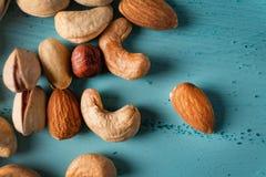 Sortiment av muttrar i träbunke på den blåa trätabellen Kasju hasselnötter, mandlar royaltyfria foton