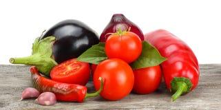 Sortiment av nya rå grönsaker på den gamla trätabellen med vit bakgrund Tomat aubergine, lök, chilipeppar arkivbilder