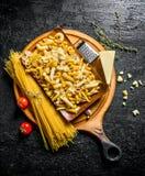 Sortiment av olika typer av r? deg p? en sk?rbr?da med parmesan och tomater arkivbilder