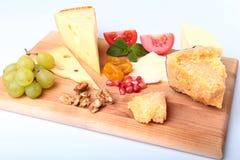 Sortiment av ost med frukter, druvor, muttrar och ostkniven på ett träportionmagasin Arkivbilder