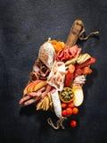 Sortiment av salami och mellanm?l Korv Fouet, korvar, salami, paperoni P? en svart tr?bakgrund Top besk?dar Fritt utrymme f?r royaltyfri foto