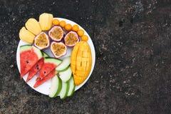 Sortiment av skivade tropiska frukter på plattan Bakgrund av den mörka stenen arkivbilder