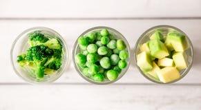 Sortimentet av gräsplan klippte grönsaker i skottexponeringsglas på vit bakgrund Royaltyfria Foton