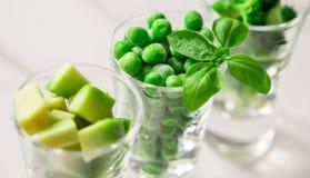 Sortimentet av gräsplan klippte grönsaker i skottexponeringsglas på vit bakgrund Royaltyfri Foto