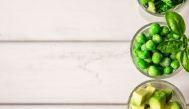 Sortimentet av gräsplan klippte grönsaker i skottexponeringsglas på vit bakgrund Royaltyfria Bilder