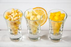 Sortimentet av guling klippte grönsaker i skottexponeringsglas på vit bakgrund Royaltyfria Foton