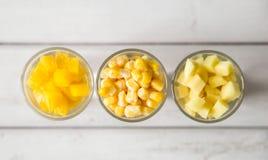 Sortimentet av guling klippte grönsaker i skottexponeringsglas på vit bakgrund Arkivbild