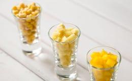 Sortimentet av guling klippte grönsaker i skottexponeringsglas på vit bakgrund Fotografering för Bildbyråer