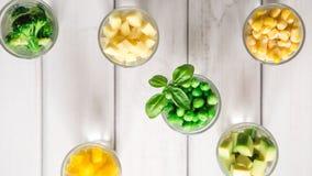 Sortimentet av guling och gräsplan klippte grönsaker i skottexponeringsglas på vit bakgrund Royaltyfria Foton