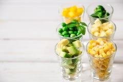 Sortimentet av guling och gräsplan klippte grönsaker i skottexponeringsglas på vit bakgrund Arkivfoto