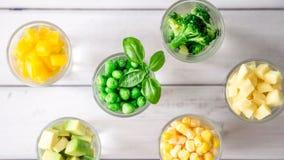 Sortimentet av guling och gräsplan klippte grönsaker i skottexponeringsglas på vit bakgrund Royaltyfri Foto