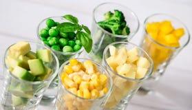Sortimentet av guling och gräsplan klippte grönsaker i skottexponeringsglas på vit bakgrund Fotografering för Bildbyråer