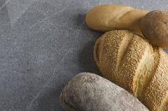 Sortimentet av läckert bröd på grå färger stenar tabellen i köket royaltyfria bilder