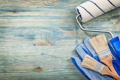 Sortimentet av målarfärgrullen borstar skyddande handskar på den wood boaen arkivfoton