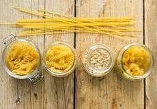 Sortimentet av torr pasta för italienare i exponeringsglaset skorrar på träbakgrunden Fotografering för Bildbyråer