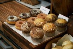 Sortimentmuffin och donuts på trätabellen Frukostbuffé c arkivbild