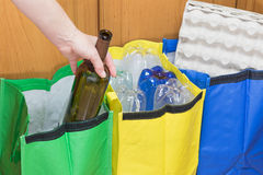 Sorting glass waste. Female hand is sorting empty wine bottle to the green bag. Household Waste concept royalty free stock photography