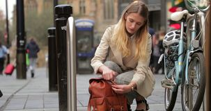 Sorting Through her Backpack. Low angle view of a young businesswoman squatting next to bike racks as she packs her backpack stock video