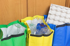 Sorting Household Waste concept. Green, blue and yellow bags for sorting household waste are filled with waste - paper, plastic and glass stock image