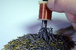 Sorting iron from brass. A mix of brass and iron nails are easily sorted with an electromagnet Stock Image