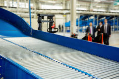 Sorting line in Large warehouse. Sorting line with roller conveyor system for transporting crates in large modern warehouse with forklifts royalty free stock photos