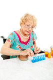 Sorting Medication for the Week. Senior woman in wheelchair sorting her medication for the week.  White background Royalty Free Stock Photography