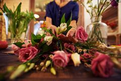 Sorting out flowers. Female florist sorting fresh flowers in workshop stock image