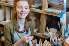Beaming good-looking ginger girl holding professional paintbrush. Sorting out paintbrushes. Beaming good-looking ginger girl holding professional paintbrush and stock photos