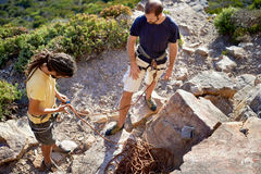 Sorting out the rope to climb. Two men about to go rock climbing and attaching the climbing rope to their harness Royalty Free Stock Photos