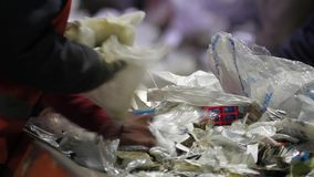 Recycling factory workers. Sorting paper and plastic on a conveyor belt in a recycling facility. Trash workers sorting trash, garbage at a recycling plant stock video footage