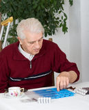 Sorting pills. Senior man sorting his drugs in blue plastic pill container Stock Photography