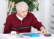 Sorting pills. Senior man sorting his drugs in blue plastic pill container Royalty Free Stock Images