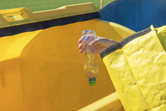 Sorting plastic hosehold waste concept. The woman is throwing a plastic bottle from yellow portable bag to yellow container for sorting plastic household waste royalty free stock photos