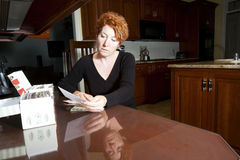 Sorting recipes. Female sorting recipe cards at a kitchen table Royalty Free Stock Photo