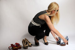 Sorting shoes. Woman  with long blond hair arranging her shoes Royalty Free Stock Photos