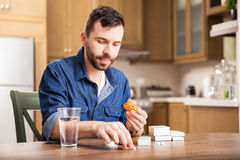 Sorting some of my pills at home. Young man with a beard organizing his medicine in a pill box at home Stock Image