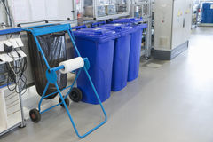 Sorting of waste into the bins in the assembly factory. Sorting of waste into the prepared blue bins in the production hall of assembly factory. All potential royalty free stock photos