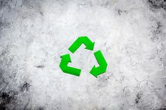 Sorting waste and recycle. Green paper recycling sign on grey background top view space for text. Sorting waste and recycle. Green paper recycling sign on grey Stock Photos