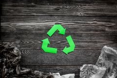 Sorting waste and recycle. Green paper recycling sign on grey wooden background top view space for text. Sorting waste and recycle. Green paper recycling sign on Royalty Free Stock Photography