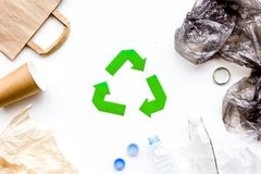 Sorting waste and recycle. Green paper recycling sign among waste paper, plastic, glass, polyethylene on white. Background top view royalty free stock photography