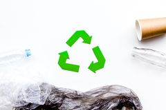 Sorting waste and recycle. Green paper recycling sign among waste paper, plastic, glass, polyethylene on white. Background top view stock image