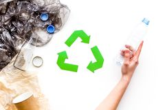 Sorting waste and recycle. Green paper recycling sign among waste paper, plastic, glass, polyethylene on white. Background top view stock photo