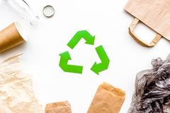 Sorting waste and recycle. Green paper recycling sign among waste paper, plastic, glass, polyethylene on white. Background top view royalty free stock images