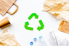 Sorting waste and recycle. Green paper recycling sign among waste paper, plastic, glass, polyethylene on white. Background top view stock photography