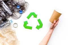 Sorting waste and recycle. Green paper recycling sign among waste paper, plastic, glass, polyethylene on white. Background top view stock photos