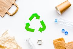 Sorting waste and recycle. Green paper recycling sign among waste paper, plastic, glass, polyethylene on white. Background top view royalty free stock photos